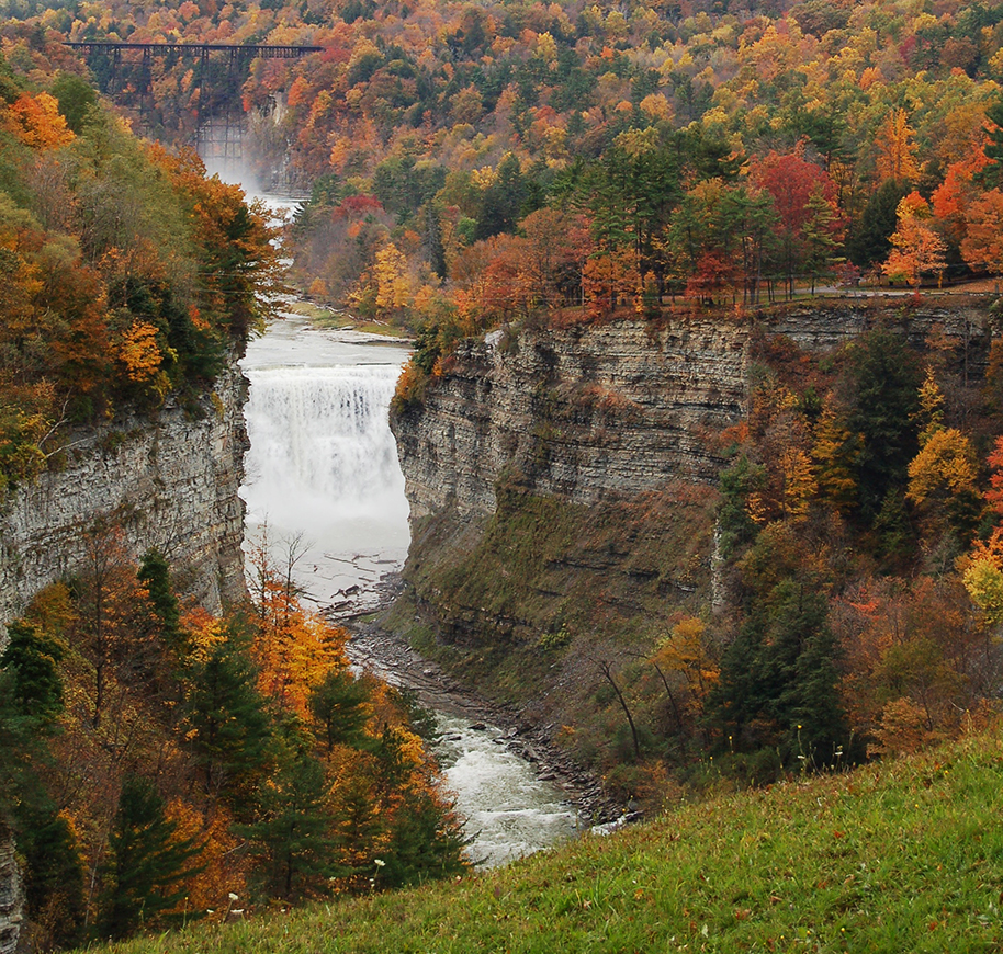Picture of a waterfall surrounded by large canyon walls and colorful fall trees in full bloom.